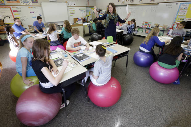 "Robbi Giuliano teaches her fifth grade class as they sit on yoga balls at  Westtown-Thornbury Elementary School  Monday, Feb. 4, 2013, in West Chester, Pa.  Giuliano says ""I'm able to get a lot done with them because they're sitting on yoga balls.""   (AP Photo/Matt Rourke)"