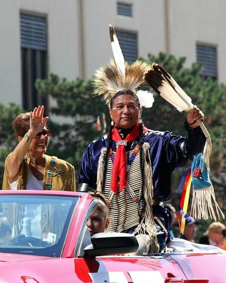 Gerry Bonds and Terry Tsotigh (Kiowa) wave to onlookers at the Red Earth Festival Parade in downtown Oklahoma City. (Photo provided)
