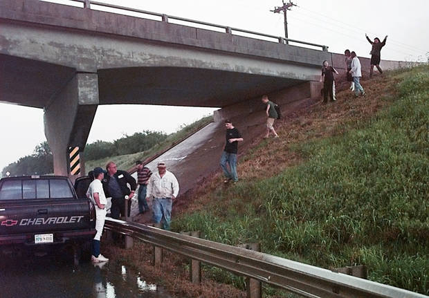 May 3, 1999, Oklahoma City Tornado:  Tornado victims: People crawling out from under a bridge at SW 134th and I-44 after watching the tornado cross the highway east into Moore, Okla.  Staff Photo by Paul Hellstern