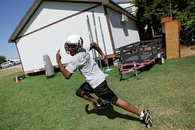HIGH SCHOOL FOOTBALL: Marcus Smith, runs passing drills past an equipment shed and other equipment during football practice at Seeworth Academy  in Oklahoma City on Wednesday, August 25, 2010. The team practices on a small yard on the southeast side of the Seeworth campus. Photo by John Clanton, The Oklahoman ORG XMIT: KOD