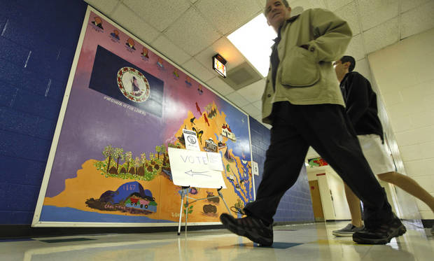 Voters walk past a mural of the state of Virginia as they go to vote in a polling place located in an elementary school in Richmond, Va., Tuesday, Nov. 6, 2012. Americans are heading into polling places across the country Tuesday.(AP Photo/Steve Helber)