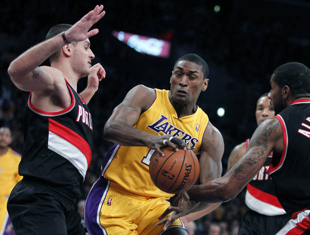 Los Angeles Lakers forward Metta World Peace, center, splits between the defense of Portland Trail Blazers guard Sasha Pavlovic, left, of Montenegro, and Trail Blazers forward LaMarcus Aldridge, right, during the first quarter of an NBA basketball game, Friday, Dec. 28, 2012, in Los Angeles.  (AP Photo/Alex Gallardo)
