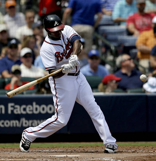 Atlanta Braves' Justin Upton swings to hit a single in the fourth inning of a baseball game against the Kansas City Royals, Wednesday, April 17, 2013, in Atlanta. (AP Photo/David Goldman)