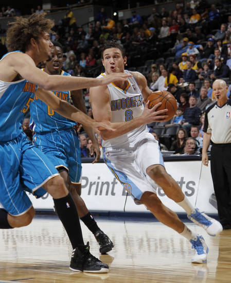New Orleans Hornets cnter Robin Lopez, front left, and forward Al-Farouq Aminu, back left, cover Denver Nuggets forward Danilo Gallinari, of Italy, who drives for a shot in the first quarter of an NBA basketball game in Denver, Friday, Feb. 1, 2013. (AP Photo/David Zalubowski)