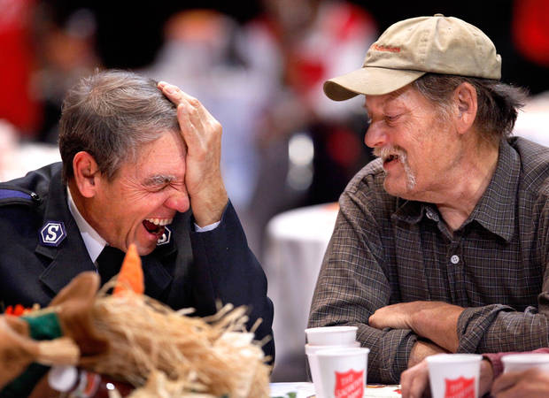 Ernie Potter, left, with the Salvation Army, erupts into laughter as he talks to Larry Bowman at a breakfast table. The Salvation Army prepared food for 1,000 breakfast guests at the Bricktown Coca-Cola Events Center on Thanksgiving morning, Nov. 25,  2010. Photo by Jim Beckel, The Oklahoman