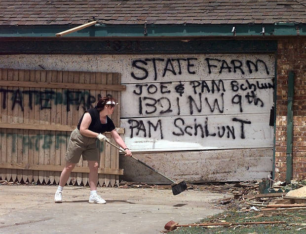 MAY 3, 1999 TORNADO: Tornado victims, damage: Pam Schlunt sweeps off the driveway in front of her home damaged in Monday night's torando in Moore. The message on the door is to the insurance company.