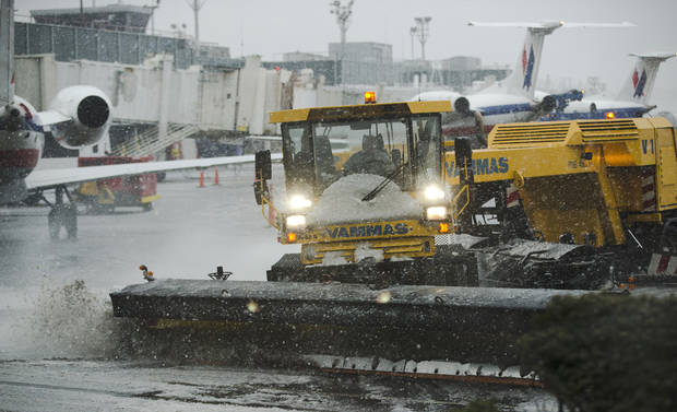 Grounds crews clear the tarmac at LaGuardia Airport in New York Friday, Feb. 8, 2013. Airlines scratched more than 3,700 flights in the Northeast through Saturday as snow began falling in what was predicted to be a huge blizzard that could dump 1 to 3 feet of snow from New York City to Boston and beyond. (AP Photo/Frank Franklin II) ORG XMIT: NYFF116