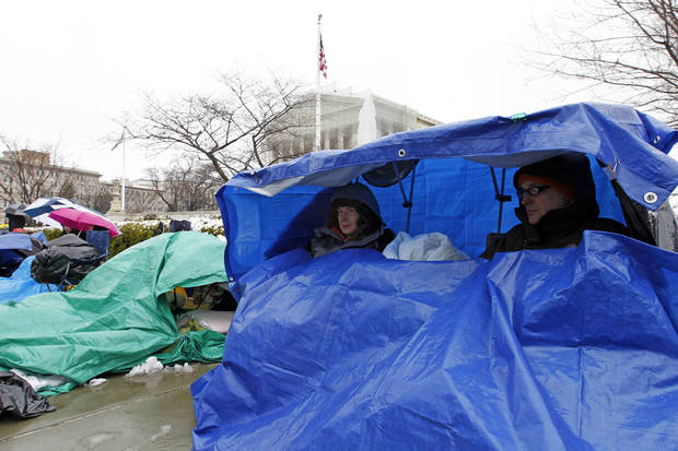 Joey Williamson, left, and Gary Brown form New York City, cover themselves from the snow as they wait in line outside of the Supreme Court in Washington, Monday March, 25, 2013, a day before the  court hearing on same-sex marriage. (AP Photo/Jose Luis Magana)