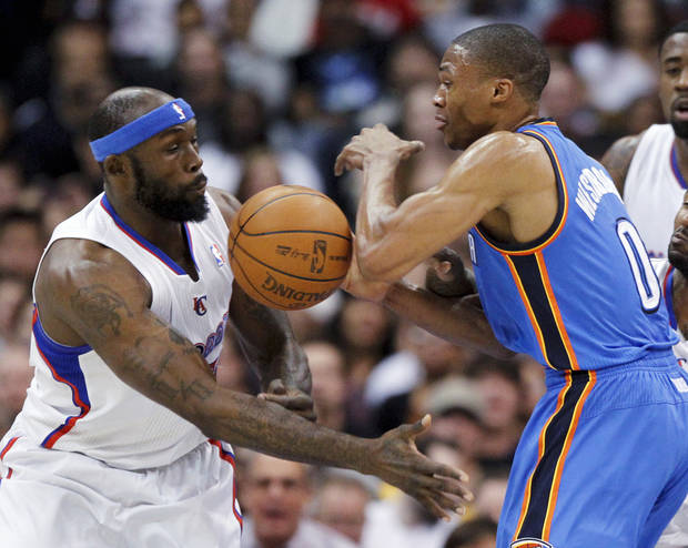 Los Angeles Clippers forward Reggie Evans, left, battles Oklahoma City Thunder guard Russell Westbrook for a loose ball during the first half of an NBA basketball game in Los Angeles, Monday, Jan. 30, 2012. (AP Photo/Chris Carlson) ORG XMIT: LAS102
