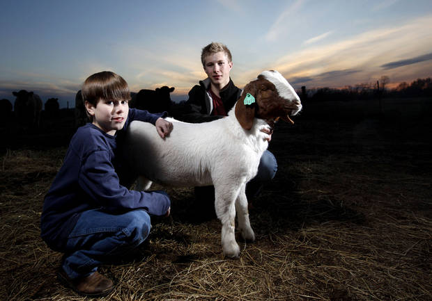 Carson, right,  and Garrett Lough pose with a goat at a barn in Hennessey, Okla., Thursday, Feb. 16, 2012. Photo by Sarah Phipps, The Oklahoman