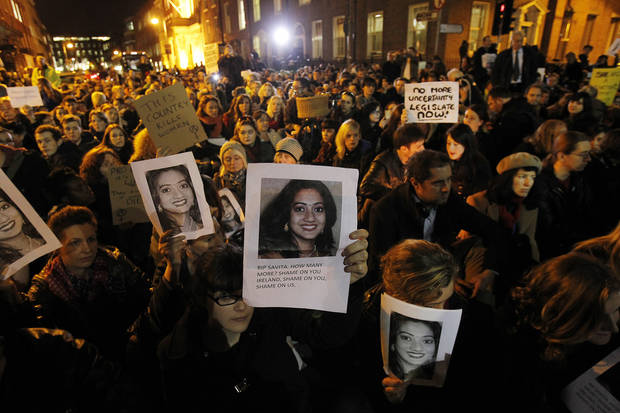 Protestors outside Leinster House in Dublin Wednesday Nov. 14, 2012 against the death in October of Savita Halappanavar, pictured, a dentist aged 31, who was 17 weeks pregnant, after suffering a miscarriage and septicaemia. The woman's husband Praveen Halappanavar claims she had complained of being in agonising pain while in Galway University Hospital. He has said that doctors refused to carry out a medical termination because the foetus's heartbeat was present. Ireland's constitution officially bans abortion, but a 1992 Supreme Court ruling found the procedure should be legalized for situations when the woman's life is at risk from continuing the pregnancy. (AP Photo/ Julien Behal, PA)