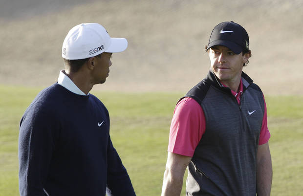 Rory McIlroy from Northern Ireland, rear, and Tiger Woods from U.S. talk on the 13th hole during the first round of Abu Dhabi Golf Championship in Abu Dhabi, United Arab Emirates, Thursday, Jan. 17, 2013. (AP Photo/Kamran Jebreili)