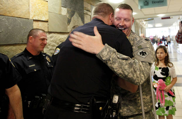 Edmond Police Sgt. Damon Minter, Edmond Police officer Kyle Stoy and Oklahoma National Guard soldier returns home at Will Rogers World Airport in  Oklahoma City, Thursday, March 22, 2012. Photo by Sarah Phipps, The Oklahoman.