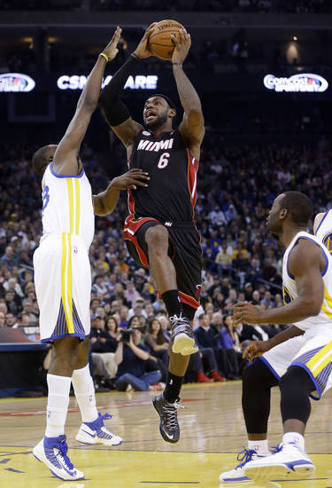 Miami Heat's LeBron James (6) shoots next to Golden State Warriors' Draymond Green, left, during the first half of an NBA basketball game in Oakland, Calif., Wednesday, Jan. 16, 2013. James on Wednesday became the youngest player in NBA history to score 20,000 points. (AP Photo/Marcio Jose Sanchez)