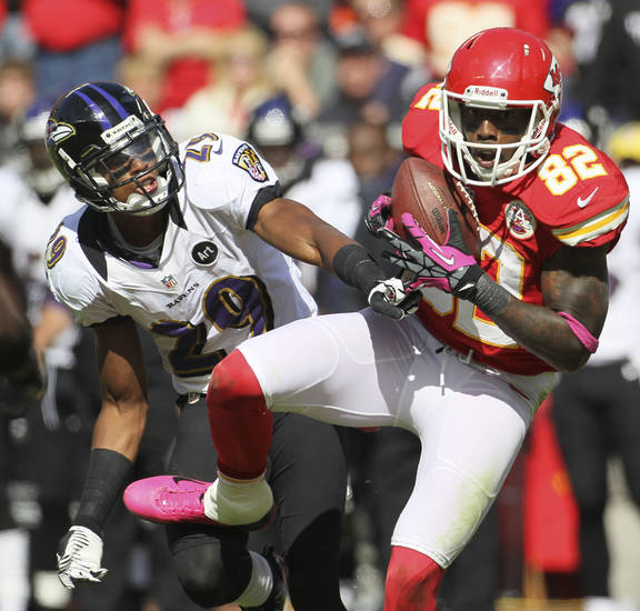   Kansas City Chiefs wide receiver Dwayne Bowe (82) catches a pass while covered by Baltimore Ravens cornerback Cary Williams (29) during the second half of an NFL football game at Arrowhead Stadium in Kansas City, Mo., Sunday, Oct. 7, 2012. (AP Photo/Colin E. Braley)  
