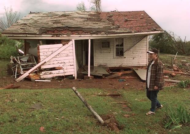 MAY 3, 1999 TORNADO: Tornado damage. Angie McNeil surveys her grandmother's house after a collapsed water tower in Mulhall washed it twelve feet off its foundation.  Kathryn Harris, 76, was alone in the house at the time.