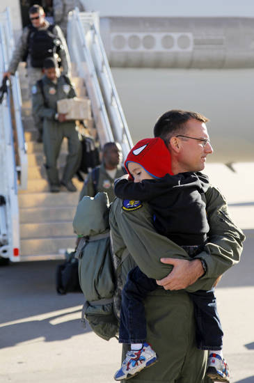 Airmen exit an E-3 AWACS aircraft as 1st Lt. Joshua Albritton holds his son Isaac Albritton, 3-and-a-half,  after arriving at Tinker Air Force Base in Midwest City, Okla., Friday, Nov. 4, 2011. Approximately 40 Airmen from the 552nd Air Control Wing returned to Tinker Air Force Base after serving in support of Operation Unified Protector, part of the NATO effort to protect civilians in Libya.   Photo by Nate Billings, The Oklahoman