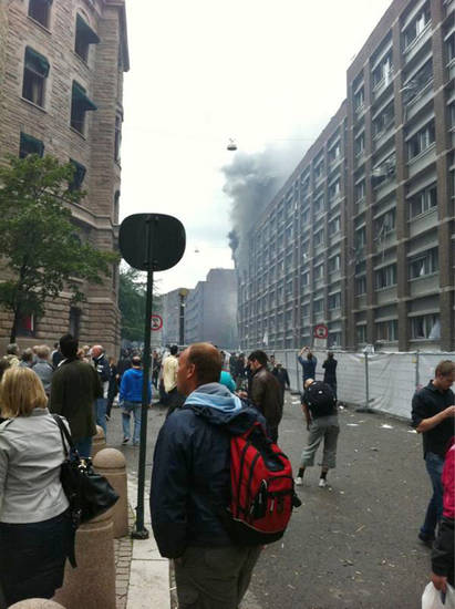 Pedestrians watch the smoke rise from government buildings in the center of Oslo, Norway, Friday, July 22, 2011, following an explosion that tore open several buildings including the prime minister's office, shattering windows and covering the street with documents. (AP Photo/Gregers Rygg