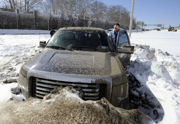 Wayne Gingo, of Medford, N.Y., gets back into his car that got stuck in the snow on the Long Island Expressway eastbound near Exit 60, Saturday, Feb. 9, 2013, in Ronkonkoma, N.Y. Gingo was driving home from his job as a postal worker at JFK Airport and got stuck in the snow at 1:45 a.m. He spent the night in the car waiting for a tow truck. (AP Photo/Kathy Kmonicek) ORG XMIT: NYKK112