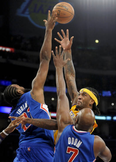 Los Angeles Lakers center Jordan Hill, center, drives between Los Angeles Clippers center Ronny Turiaf (21), of France, and teammate forward Lamar Odom (7) in the first half of an NBA basketball game, Friday, Nov. 2, 2012, in Los Angeles.(AP Photo/Gus Ruelas)
