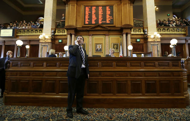 Iowa Speaker of the House Kraig Paulsen talks on his cell phone during the opening day of the Iowa Legislature, Monday, Jan. 14, 2013, at the Statehouse in Des Moines, Iowa. (AP Photo/Charlie Neibergall)