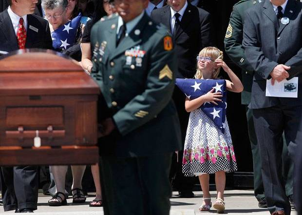 Chelsie Jirtle, 5, holds a flag given to her by soldiers as the casket for her father, U.S. Army SPC Charles Scott Jirtle, is removed, Wednesday, June 16, 2010 in Lawton, Okla.. Hundreds of mourners came to First Baptist East Church in Lawton to attend the funeral  Jirtle, 29, of Lawton was killed June 7, 2010 in the Kunar Province of Afghanistan.  (AP Photo/The Oklahoman, Jim Beckel) ORG XMIT: OKOKL101