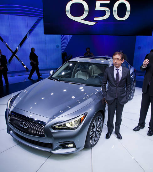 Infiniti Chief Creative Officer Shiro Nakamura stands next to the newly unveiled Q50 sedan, at the North American International Auto Show, Monday, Jan. 14, 2013, in Detroit, Mich. (AP Photo/Tony Ding)