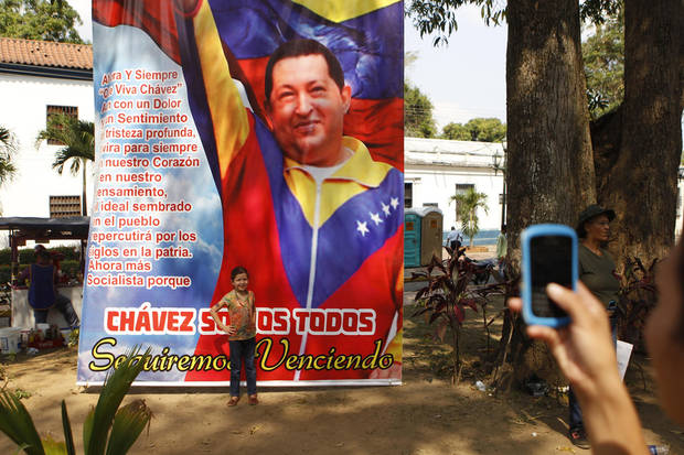 A girl posses for a photograph in front of a banner of  late President Hugo Chavez at the Bolivar square in Barinas, the capital of the state where he was born in western Venezuela, Friday, March 8, 2013. Chavez died on March 5 after a nearly two-year bout with cancer.  He was 58. (AP Photo/Esteban Felix)