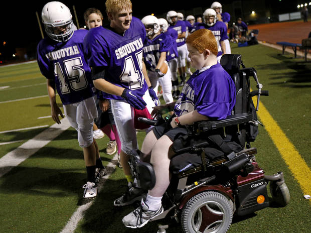 Keegan Erbst talks with Brandon Hill on the sidelines during a Sequoyah Middle School football game, Thursday, September 27, 2012. Keegan, who has muscular dystrophy and is confined to a wheelchair, got involved with the team after players Lucas Coker, Colton James, and Parker Tumleson, pushed suggested it to the coach.  Photo by Bryan Terry, The Oklahoman