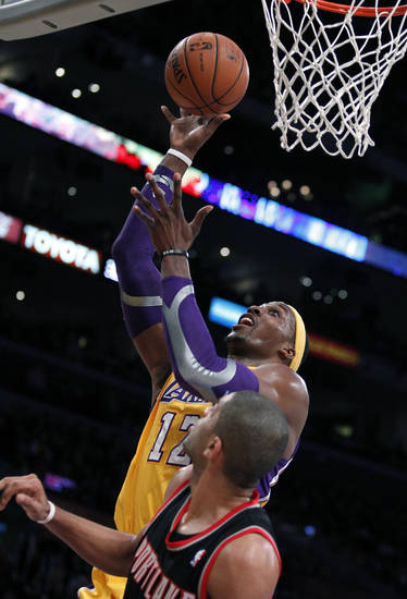 Los Angeles Lakers center Dwight Howard (12) shoots over Portland Trail Blazers small forward Victor Claver (18), of Spain, during the first quarter of an NBA basketball game, Friday, Dec. 28, 2012, in Los Angeles.  (AP Photo/Alex Gallardo)
