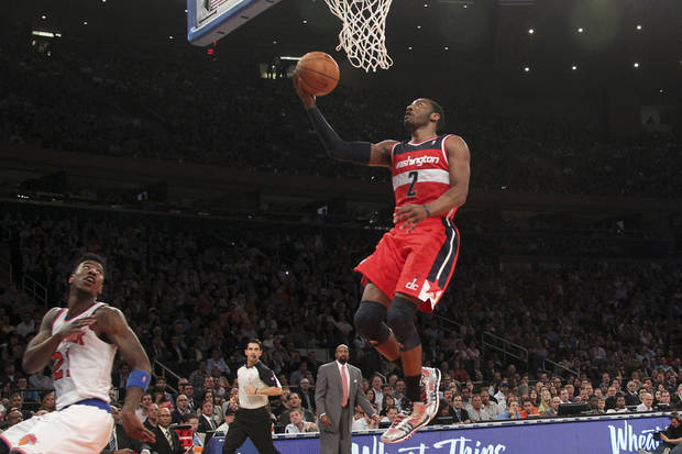 Washington Wizards' John Wall (2) scores as New York Knicks' Iman Shumpert looks on during the first half of an NBA basketball game, Tuesday, April 9, 2013, at Madison Square Garden in New York.  (AP Photo/Mary Altaffer)