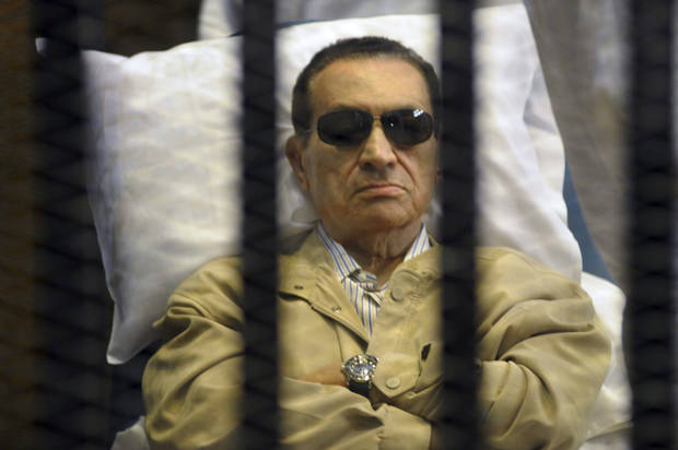 FILE - In this June 2, 2012 file photo, Egypt's ex-President Hosni Mubarak lays on a gurney inside a barred cage in the police academy courthouse in Cairo, Egypt. An Egyptian security official says ousted president Hosni Mubarak has been interrogated over gifts worth millions of Egyptian pounds (hundreds of thousands of US dollars) he allegedly received from the country's top newspaper as a show of loyalty while he was in power. Mubarak is serving a life sentence after being convicted for failing to stop killings of protesters during 2011 uprising. (AP Photo/File)