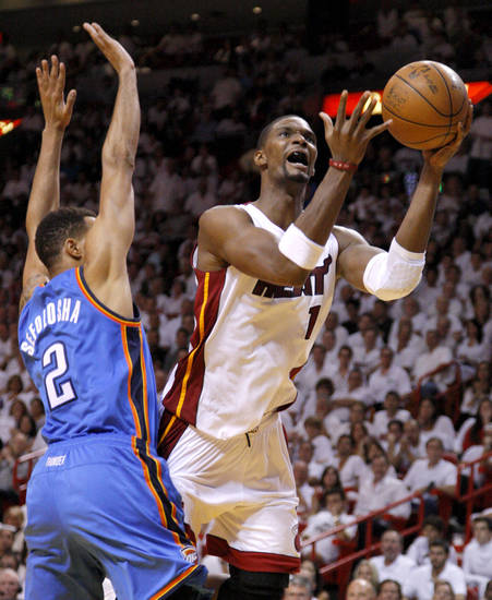 Miami's Chris Bosh (1) shoots the ball beside Oklahoma City's Thabo Sefolosha (2) during Game 4 of the NBA Finals between the Oklahoma City Thunder and the Miami Heat at American Airlines Arena, Tuesday, June 19, 2012. Oklahoma City lost 104-98.  Photo by Bryan Terry, The Oklahoman