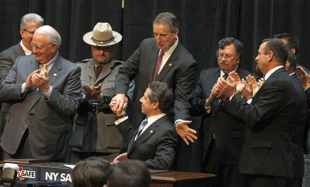 NY Gov. Andrew Cuomo, seated at center, gets a congratulatory hand shake from Lt. Gov. Robert Duffy after signing the NY Safe Act during a signing ceremony at City Hall in Rochester Wednesday, Jan. 16, 2013.  Cuomo signed into law on Tuesday  legislation  that tightens a ban on assault-style rifles, calls for background checks on ammunition purchases, outlaws large-capacity magazines and tries to keep guns out of the hands of mentally ill people deemed to be a threat.  (AP Photo/Democrat & Chronicle, Shawn Dowd)  MAGS OUT; NO SALES