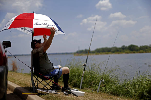 John Parson adjusts his umbrella as while fishing during his day off at Lake Hefner, Tuesday in Oklahoma City. Photo by Bryan Terry, The Oklahoman <strong>BRYAN TERRY</strong>