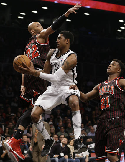 Brooklyn Nets guard MarShon Brooks (9) passes around Chicago Bulls forward Taj Gibson (22) as Bulls forward Jimmy Butler (21) watches in the first half of an NBA basketball game at the Barclays Center, Friday, Feb. 1, 2013, in New York. (AP Photo/Kathy Willens)