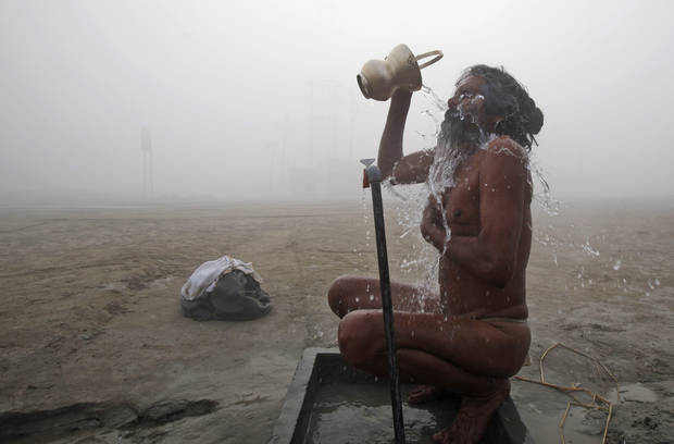A sadhu, or Hindu holy man, bathes in water from a tap on the banks of the Ganges River on a cold and foggy morning in Allahabad, India, Sunday, Dec. 30, 2012. North India continues to face extreme weather conditions with dense fog affecting flights and trains. (AP Photo/Rajesh Kumar Singh)