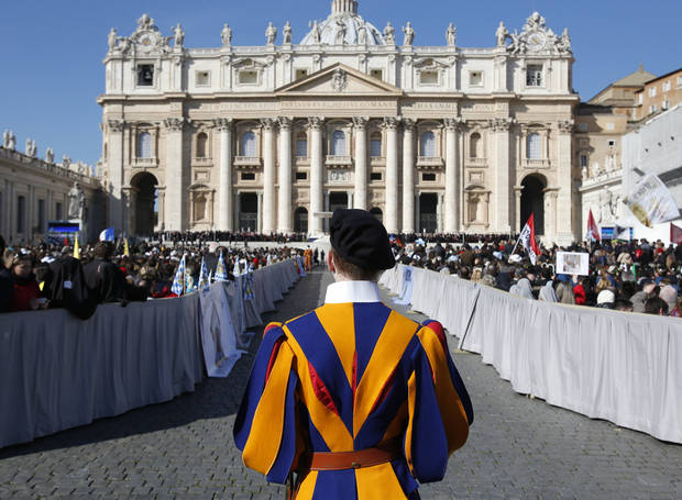 A Vatican Swiss guard stands in front of St. Peter's Basilica at the Vatican, Wednesday, Feb. 27, 2013. Pope Benedict XVI is preparing for his final general audience, the weekly appointment he kept with the faithful and tourists to teach them about the Catholic faith. (AP Photo/Michael Sohn)