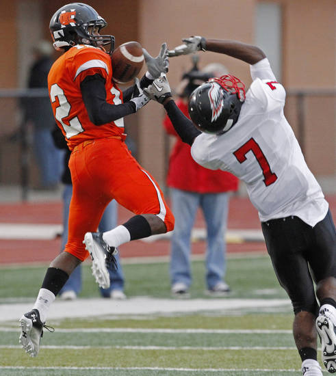 Norman's Rico Hogan (12) holds on to a pass in the first quarter over the defense of Jerell Jeter (7) as the Norman High School Tigers play the Del City Eagles on Thursday, September 15, 2011, in Norman, Okla.   Photo by Steve Sisney, The Oklahoman