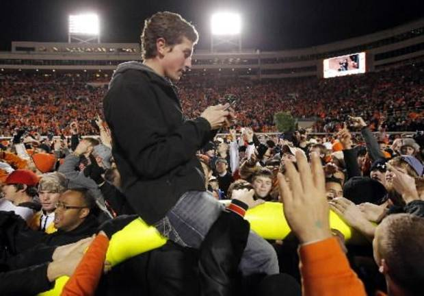 An Oklahoma State fan rides the goal post after the Cowboys&#039; 44-10 win over Oklahoma during the Bedlam college football game between the Oklahoma State University Cowboys (OSU) and the University of Oklahoma Sooners (OU) at Boone Pickens Stadium in Stillwater, Okla., Saturday, Dec. 3, 2011. Photo by Nate Billings, The Oklahoman