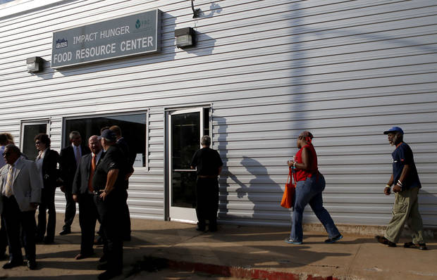 After a ribbon cutting ceremony, people enter the City Rescue Mission's new Impact Hunger Food Resource Center, 831 W California, on Wednesday.  <strong>BRYAN TERRY - THE OKLAHOMAN</strong>