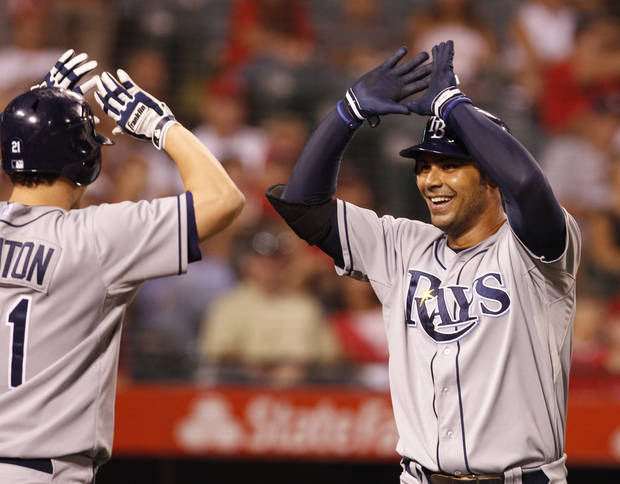 Tampa Bay Rays' Carlos Pena, right, is congratulated by Jose Lobaton after hitting a two run home run in the eighth inning of a baseball game against the Los Angeles Angels in Anaheim, Calif., on Saturday, Aug. 18, 2012. (AP Photo/Christine Cotter)
