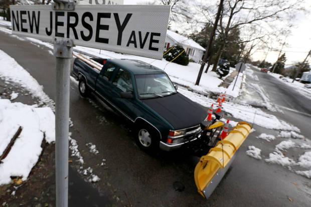 A snow plower drives on New Jersey Avenue as snow covered debris from Superstorm Sandy lies on the sidewalk, Thursday, Nov. 8, 2012, in Point Pleasant, N.J. A nor'easter hit the New Jersey shore on Wednesday, pounding the region which was already hit by Superstorm Sandy. (AP Photo/Julio Cortez)