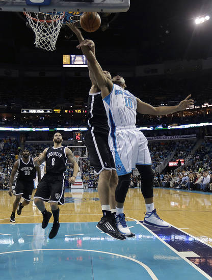 Brooklyn Nets center Brook Lopez (11) tries to block a shot by New Orleans Hornets guard Eric Gordon (10) in the first half of an NBA basketball game in New Orleans, Tuesday, Feb. 26, 2013. (AP Photo/Gerald Herbert)