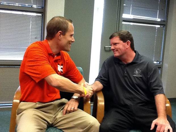 Norman principal Scott Beck and Norman North principal Bryan Young make a wager on Thursday's football opener between the schools.