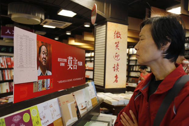 A customer looks at books written by Mo Yan, the first Chinese writer to win Nobel Prize in literature, at a book store in Shanghai, China, Saturday Oct. 13, 2012. China's newly named Nobel laureate for literature expressed hope Friday that an imprisoned Chinese winner of the Nobel Peace Prize will be freed, putting a dent in the ruling Communist Party's attempts to burnish its credentials with the latest prize. (AP Photo/Eugene Hoshiko) ORG XMIT: SHA101
