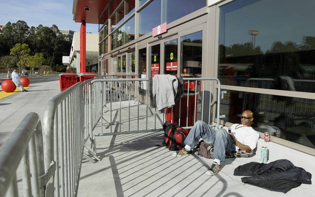 Michael Walsh waits in in line at a Target store in Colma, Calif., Thursday, Nov. 22, 2012. Walsh was the first person in line, showing up at about 6am Thursday morning. Stores typically open in the wee hours of the morning on the day after Thanksgiving known as Black Friday, named for the period when stores traditionally turn a profit for the year. But Black Friday openings have crept earlier and earlier over the past few years. Now, stores from Wal-Mart to Toys R Us are opening their doors on Thanksgiving evening, hoping Americans will be willing to shop soon after they finish their pumpkin pie. (AP Photo/Jeff Chiu)