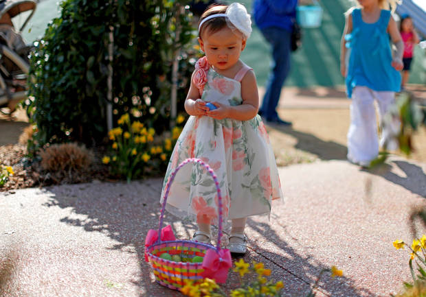 Victoria Saldivar, 17 months old, from Oklahoma City stands by her basket of eggs during the Myriad Gardens Annual Easter Egg Hunt in downtown Oklahoma City, Saturday, March 30, 2013.
