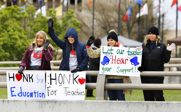 Teachers from Choctaw/Nicoma Park Schools wave to drivers below traveling on NE 23 Street during the lunch hour. Many motorists honked their car horns in support of the educators. Teachers from throughout the state converged at the Capitol to bring their concerns about education funding to the attention of legislators and state officials during the first day of a statewide public schools teacher walkout  on Monday, April 2, 2018. Photo by Jim Beckel, The Oklahoman