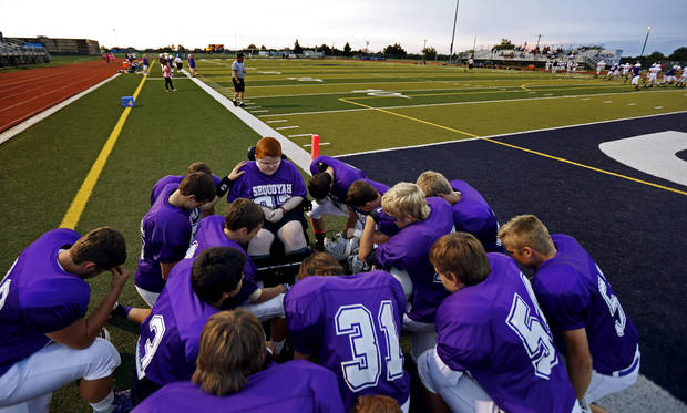 Keegan Erbst prays with the team before a Sequoyah Middle School football game, Thursday, September 27, 2012. Keegan, who has muscular dystrophy and is confined to a wheelchair, got involved with the team after players Lucas Coker, Colton James, and Parker Tumleson, pushed suggested it to the coach.  Photo by Bryan Terry, The Oklahoman